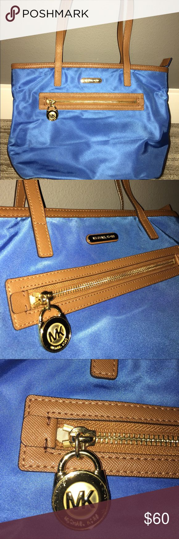 NWOT Michael Kors Blue Nylon Tote Bag Med NWOT Michael Kors Nylon Tote Bag in Blue with Brown Straps, Decorative details and bottom leather covering.  As indicated in the photos, this Tote is perfect condition.  Purchased from Nordstrom for $120.  Smoke and Pet free home. Michael Kors Bags Totes