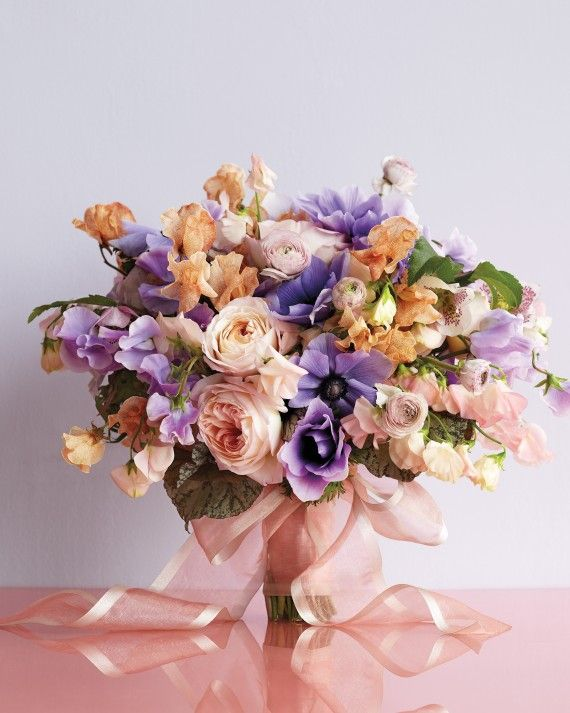 Tightly layered blush garden roses and ranunculus are accented with deep-purple anemones, speckled hellebores, mottled begonia leaves, and ruffly sweet peas in pink, lavender, and tangerine to give the eyes plenty to adore.