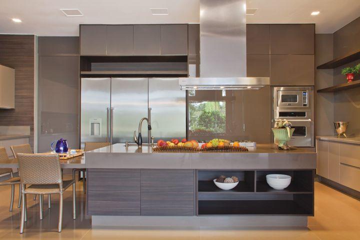A cozinha segue o mesmo padrão de bancada e móveis planejados da S.C.A. As cadeiras são em fibras naturais.