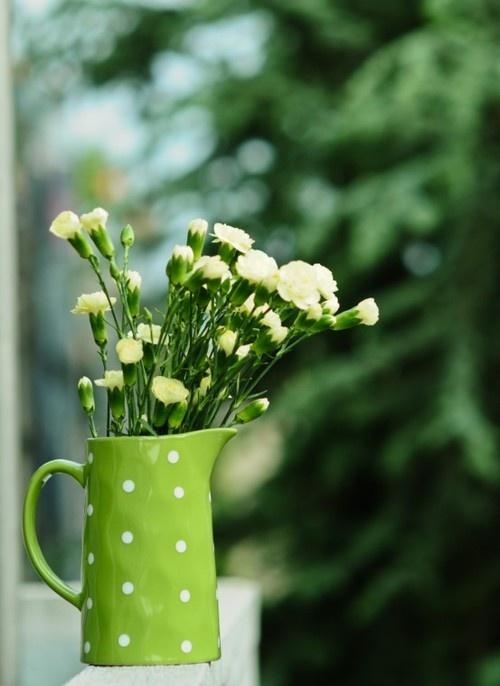 Yellow carnations in a fabulous green polka dot pitcher.