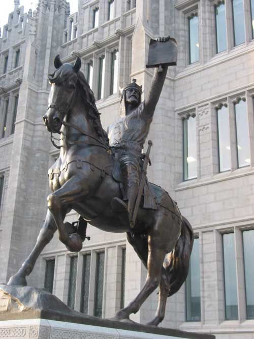 """ROBERT I """"THE BRUCE"""" King of Scotland This was an icon which was long over due in Aberdeen. The newly erected statue stands proud at Marischal College with its grand façade. The fabulous bronze sculptured image of the Bruce by Alan Beattie Heriot is seen holding up the document of the Charter which he granted to the common people of Aberdeen for lands in Aberdeen marked by a boundary of Stone markers, some of which still remain noticeable today."""