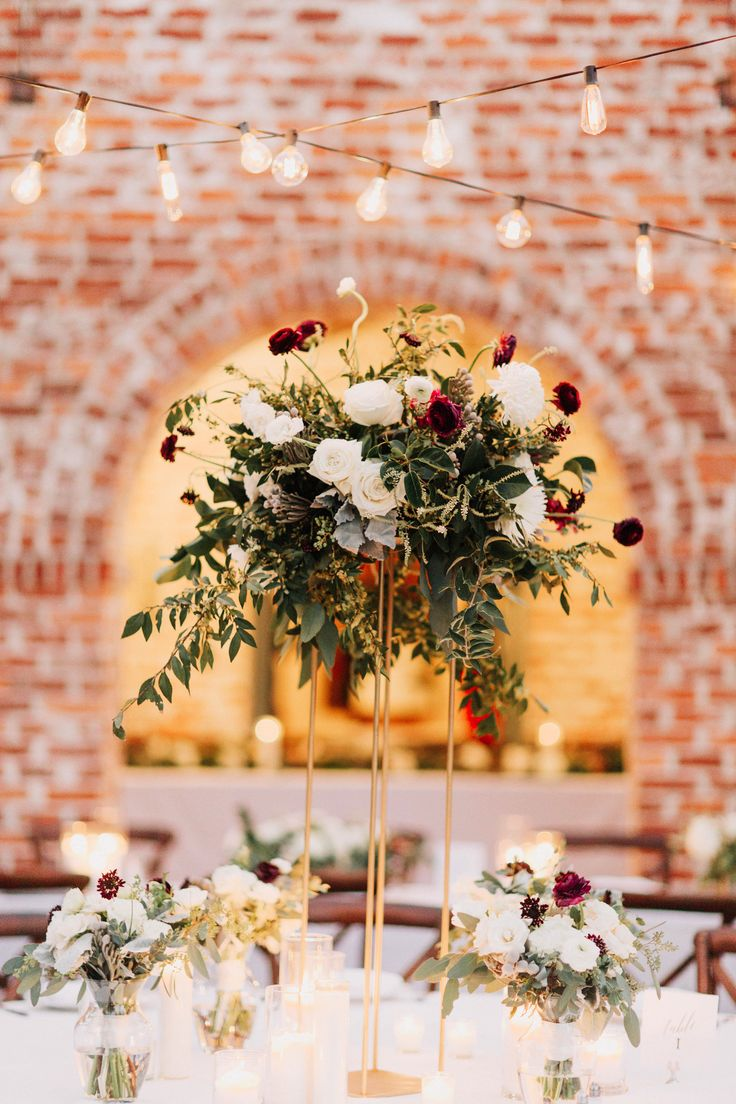 large and loose arrangement sits in the center of the reception. white majolik spray rose, burgundy scabiosa, burgundy ranunculus, white ranunculus, mondial rose, silver brunia, elm, white mums, gunei eucalyptus, seeded eucalyptus, privet berry & dusty miller  is overflowing on the top of a gold minimalist pedestal.