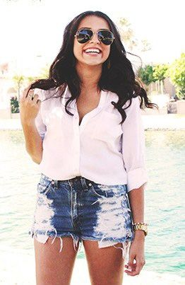 Make a button-down look casual and effortless by tucking it into a pair of denim, high-waisted shorts.
