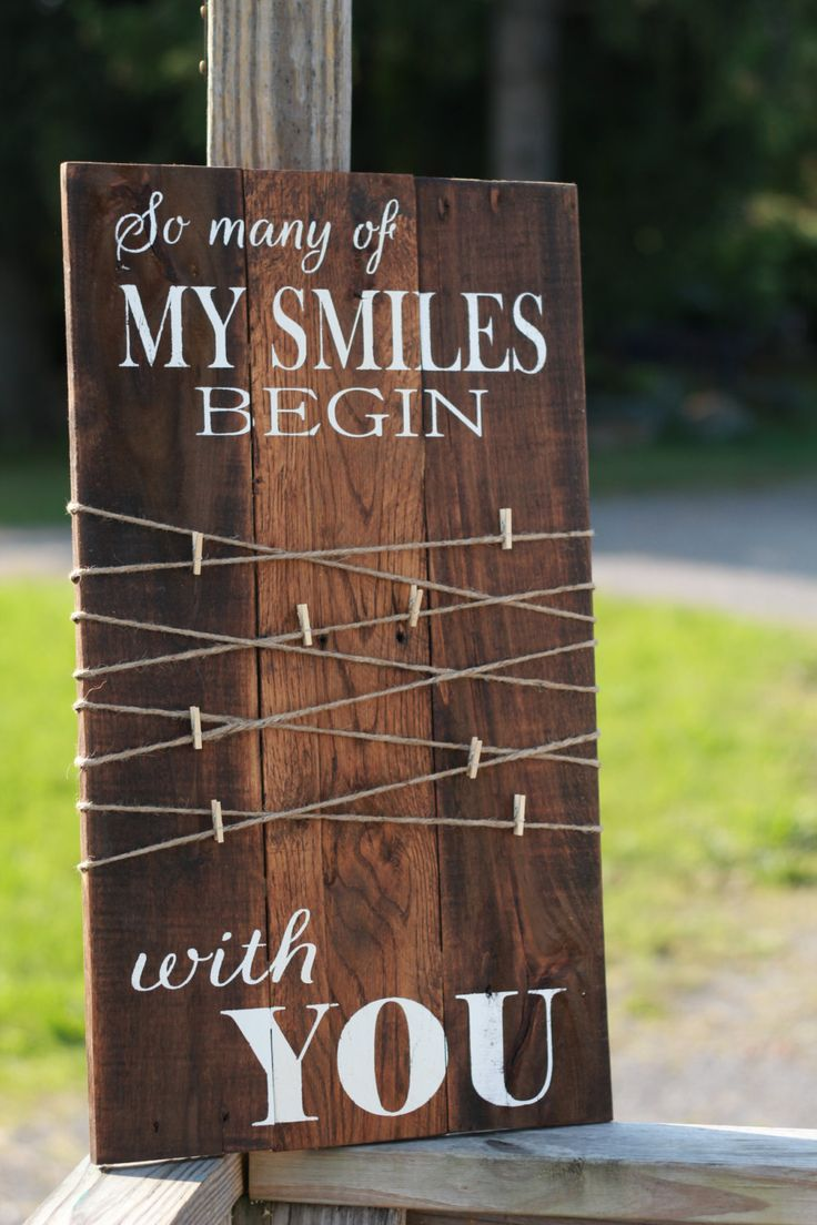 So many of my smiles begin with you.  This romantic sign would be a great addition to your rustic farmhouse décor. It would also make a lovely wedding or anniversary gift!  This beautiful rustic wood sign is made from reclaimed wood & stained in a medium dark stain. The lettering is painted in white. Twine & small clothespins are attached to create a beautiful photo display. It measures approx. 24 tall & 13 wide. Six black clothespins will be included.  This listing is for one sign, in the…
