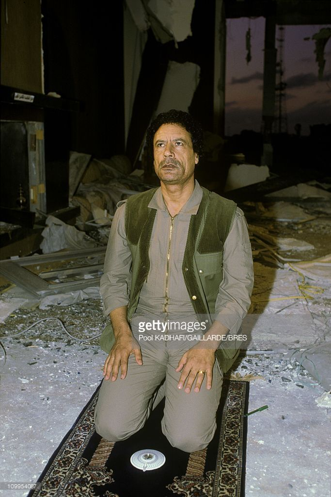 Colonel Muammar Gaddafi praying at Bab Azizia palace, destroyed in a US air raid and left in ruins, November 1986.