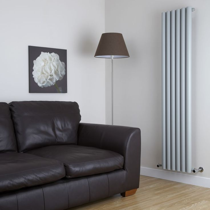 Silver column radiator with round white tube detail.