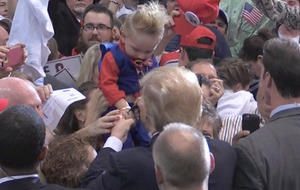 Donald Trump autographs crowdsurfing baby at campaign rally.  The baby, sucking on a Trump-themed pacifier, was a clear supporter of the Republican presidential candidate