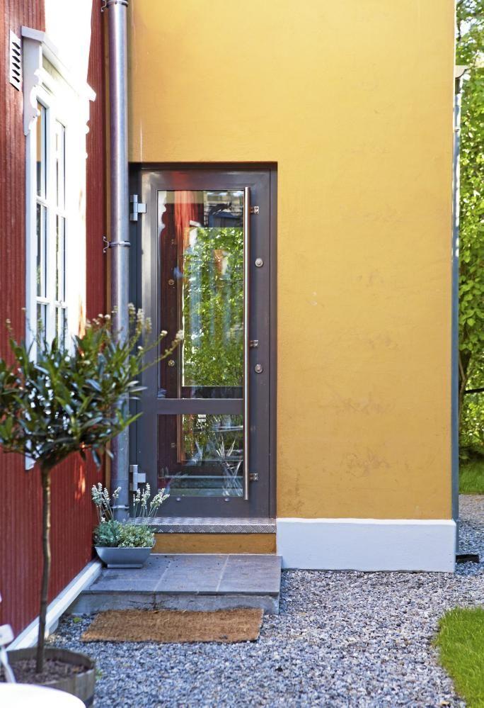 MODERNE TILBYGG. Moderne tilbygg til gammelt hus. Okergul farge og to inngangsdører i glass.