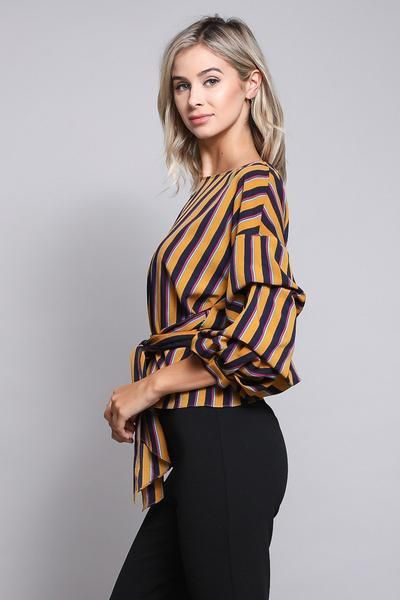 This elegant top is the perfect addition to your wardrobe. Semi-fitted through the chest and waist. Hits at the hip. Skims your shape for a relaxed, put-together silhouette.   Cut with room through the chest, arms and waist. Hits at the hip. 3/4 sleeves Wrap up sleeves Tie at waist. Imported  Fabric: 100% Polyester