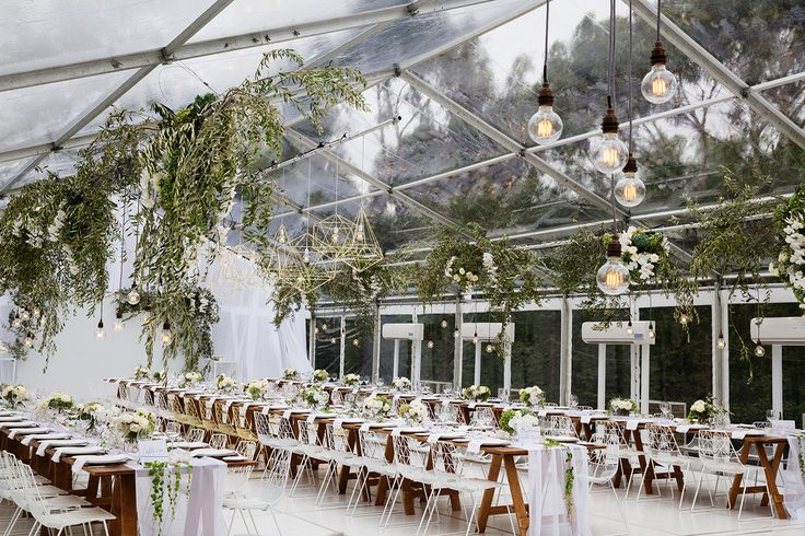 Clear Marquee wedding. Modern Classic reception. Floral installation, greenery, pendant lighting