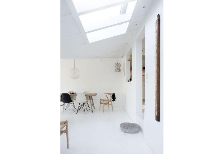 L'apertura nel tetto prosegue sopra la sala da pranzo di Vedbaek House. Attorno al tavolone vintage in legno grezzo diversi tipi di seduta: una sedia firmata Hans Wegner e le ever green Eames DSW Side Chair di Vitra in versione bianca