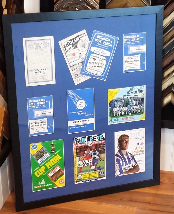 Eighty years of Brighton & Hove Albion FC programmes, framed without any glue or tape by slotting them into a recess made from foam board behind the mount.
