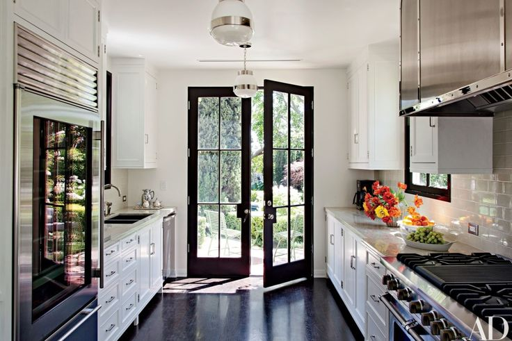The kitchen, designed by Madeline Stuart, is equipped with pendant lights from BK Antiques, a Sub-Zero refrigerator, a Blanco sink with Kallista fittings, and a Viking range.   archdigest.com