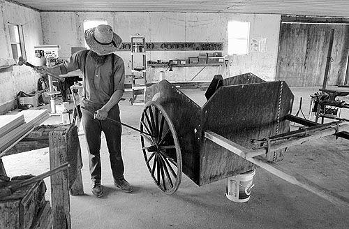 Amish man repairing a cart