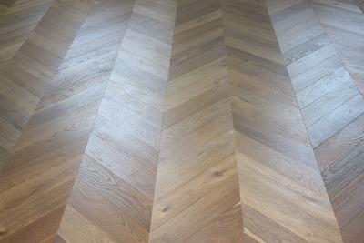 Smoked oak engineered parquet flooring laid in a chevron pattern