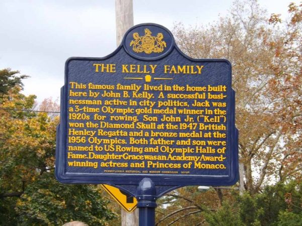 "The Kelly Family Historical Marker. Text: This famous family lived in the home built here by John B. Kelly. A successful businessman active in city politics, Jack was a 3-time Olympic gold medal winner in the 1920s for rowing. Son John Jr. (""Kell"") won the Diamond Scull at the 1947 British Henley Regatta and a bronze medal at the 1956 Olympics. Both father and son were named to US Rowing and Olympic Halls of Fame. Daughter Grace was an Academy Award-winning acress and Princess of Monaco."