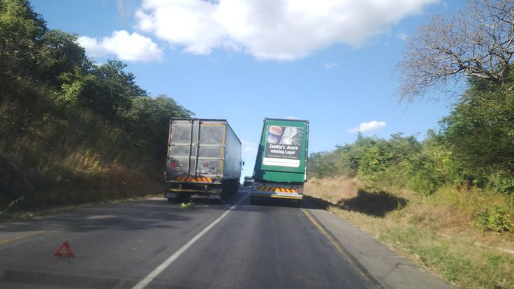 On the most hilly part of the Munali hills, a truck has broken down and is stuck/ parked right in the left lane on an uphill where overtaking is not allowed. The 'Mosi' beer truck takes the risk to overtake while an oncoming truck in the same lane can be spotted in between the trucks! [Improve our Safety on the Roads]