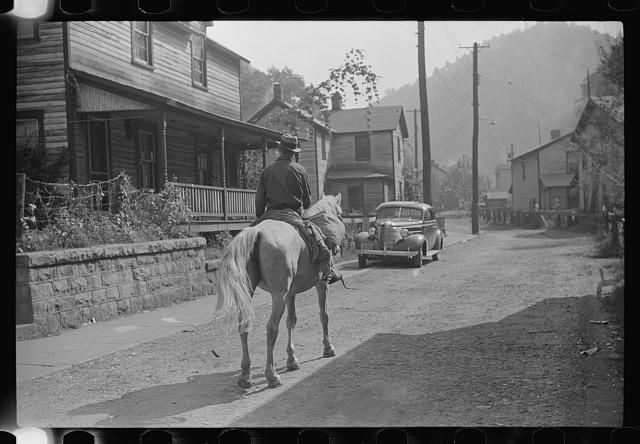 Miner taking home provisions, Caples, West Virginia, 1938. Capels is an unincorporated community on the Tug Fork River in McDowell County, West Virginia, United States.