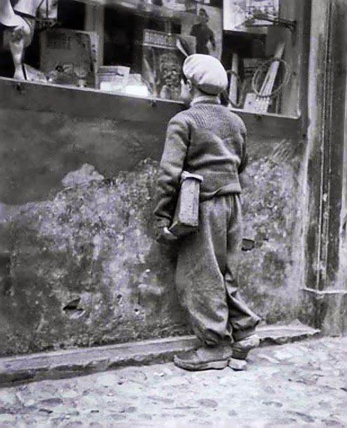 Enrico Pasquali - Comacchio, Bambino che guarda una vetrina di giocattoli, 1955. Ricordo della mia prima borsa di scuola fatta di cartone.