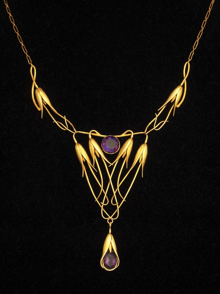 An Art Nouveau gold and amethyst necklace, French, early 1900s. Crafted in the form of a cluster of downward pointing slender bell-shaped flowers on long sweeping stems fashioned in gold wirework. Suspended at each side below a pair of side attachments formed as single flowers. A little drop set with a matching stone completes a very elegant design.