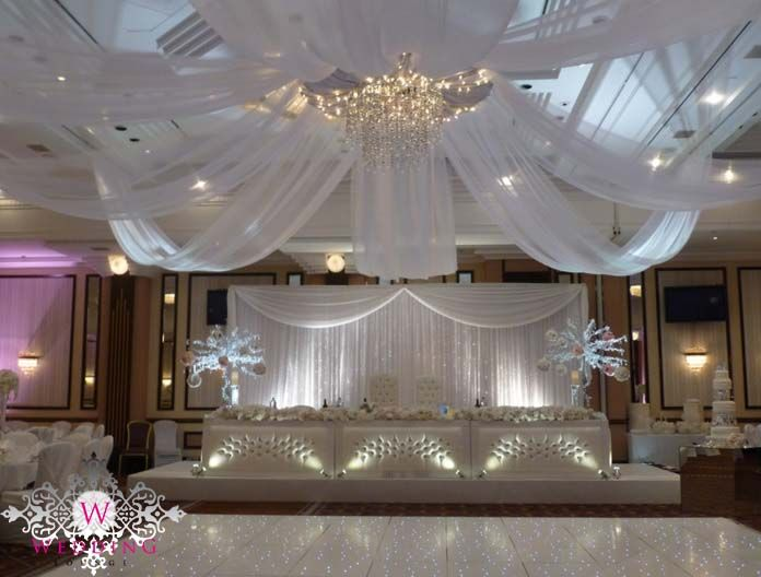 Ceiling canopy with beaded chandelier. Dancefloor, padded head table, fantasy trees, crystal head table and uplighting all by the wedding lounge. www.theweddinglounge.com