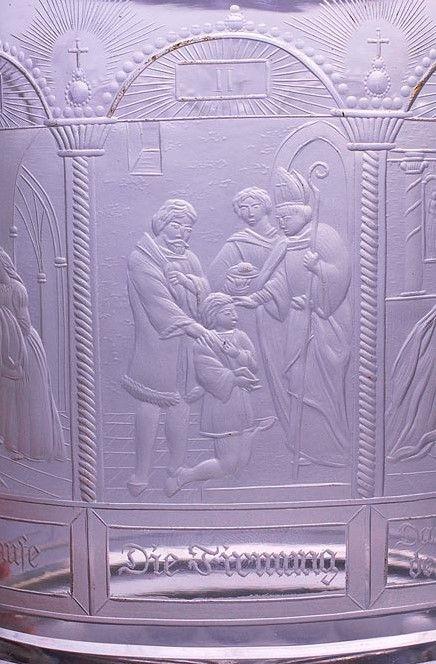 """Detail- Číše s vyobrazením Sedmi svátostí. Čechy, Jablonec nad Nisou, řezal Anton Simm, kolem 1830. Silnostěnná válcovitá číše z broušená čiré skloviny s laločnatým okrajem a radiálně uspořádanými řezy na spodní straně, plášť s náročně řezaným religiózním námětem sedmi křesťanských svátostí, v obloukovitých arkádách jsou provedeny řezby ilustrující jednotlivá znamení zprostředkující boží milost s příslušným textem, signováno v sedmém poli vpravo dole """"AS"""". Stav A, v. 16,2 cm. Anton Simm…"""