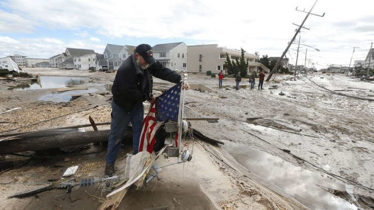 Robert Bryce sets up a U.S. flag he pulled from rubble while walking on Route 35 in Seaside Heights, N.J., a beach community that was hammered by superstorm Sandy, Wednesday, Oct. 31, 2012. (AP Photo/Julio Cortez