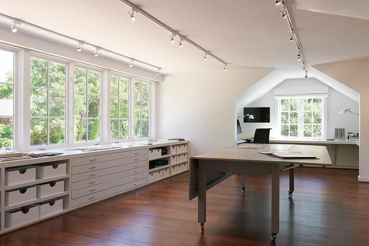 Chic office features a series of track lighting illuminating a freestanding gray folding desks on wheels placed before built-in shelves and drawers placed under windows.