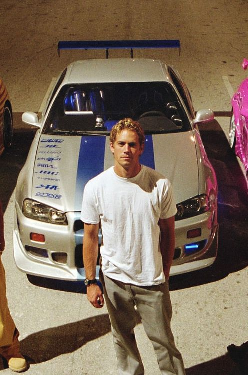 a shot of Paul Walker in front of his well known F&F 2 Nissan Skyline GTR R34
