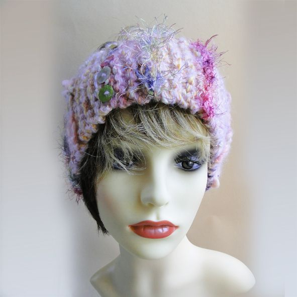 This eye catching chunky head band is hand knitted in multi coloured pink yarn with hints of purples and yellows.  This girly headband is finished off with a variety of interesting fancy eylash yarns and hand made braids with multi-coloured pearl buttons added as a detail. Stand out on the ski slopes this season with our luxury, funky chunky ski headbands