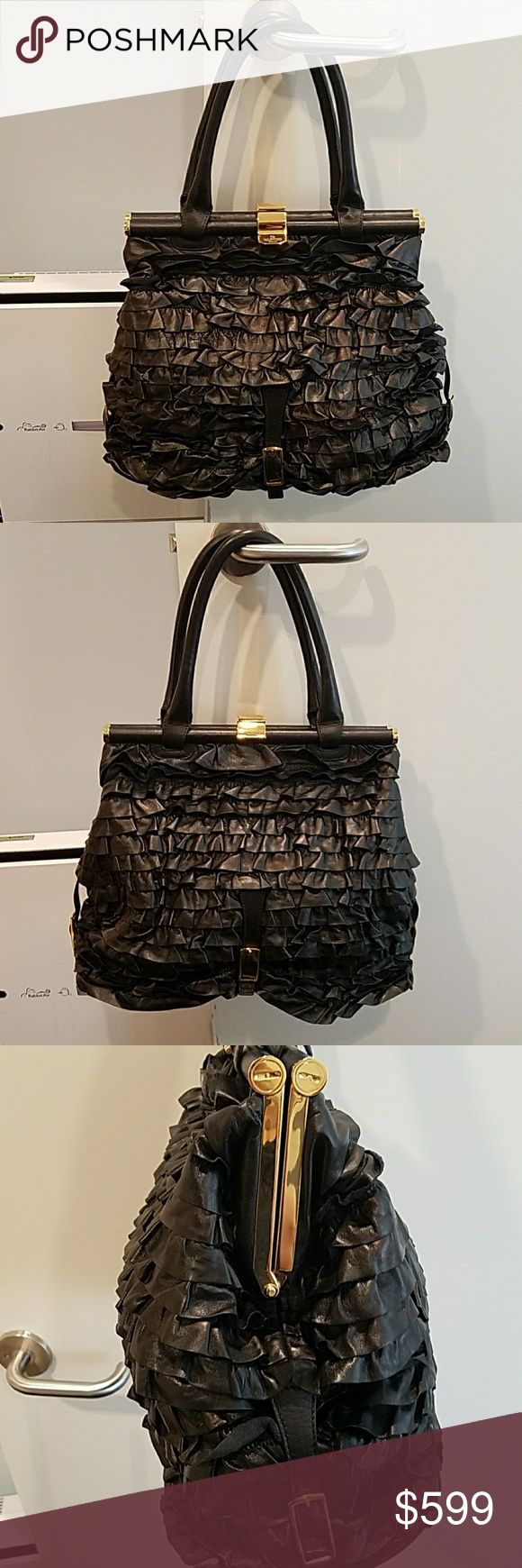 Valentino Garavani Black Leather Ruffled Tote Bag 100% Authentic Valentino Garavani Bag! Black Leather with a ruffled leather exterior and a black fabric interior. Gold colored metal hardware is pristine and free of scratches! Bottom studs still have plastic covering. This bag has only been worn a few times, so is in very good condition. Minor, unnoticeable scuff marks along the opening and one very small makeup stain on the interior lining of the bag. Valentino Garavani Bags Totes