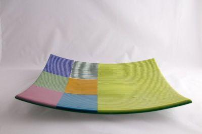 Firkantet fad gul/grøn striber, med mange farvet stribet firkanter.