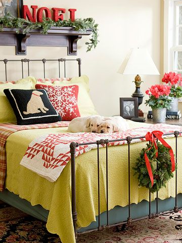 Red and green bedding paired with fresh greens create festive Christmas decor.