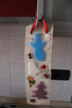 https://flic.kr/p/Bs5WoB | DECORAZIONE NATALIZIA DA APPENDERE – REALIZZATA IN CERA | Decorazione natalizia formata da una striscia di iuta, con un pupazzo di neve azzurro, una campana bianca e un albero color glicine, tutti relizzati in cera + vere bacche rosse, una coccinellina di plastica e un adesivo a forma di bastoncino natalizio. Ha inoltre un nastrino di raso rosso per appenderla. Dimensioni: 270 x 80 mm. Alla profumazione 100% naturale di lavanda.  Artigianale.  Per saperne di più…