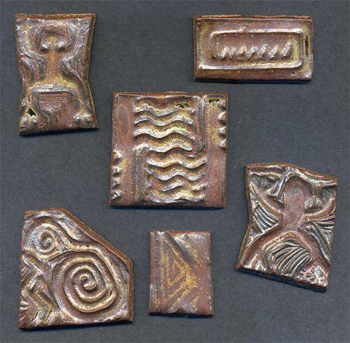 These tiles were made by hand carving rubber stamps and pressing them into stoneware clay. They were glaze fired to Cone 10.  Here is a tutorial I wrote about carving rubber stamps: http://www.limegreennews.com/howcarv.html  And here is another about making ceramic tiles from rubber stamps: http://www.carolynsstampstore.com/catalog/mosaic_table_top_with_textured_clay_tiles.php