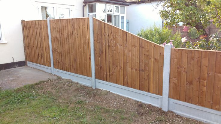 Feather Edged Fence panels and Concrete Recessed Gravel Boards in Concrete Posts, including sloping panel.