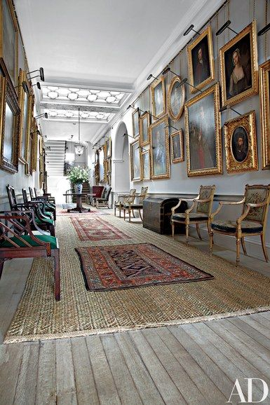 Portraits fill the walls of a skylit gallery, which contains cockpen chairs (possibly by Chippendale) as well as Louis XVI–style gilt-wood armchairs by R. Whytock & Co.; traditional rush matting is scattered with small rugs | archdigest.com