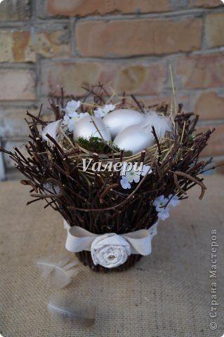 Дорогие мастерицы! Делюсь вот таким вариантом пасхального гнезда, которым можно украсить дом к Пасхальным праздникам - например, каминную полку, подоконник или праздничный стол. Для него понадобились веточки деревьев, яйца из дерева, окрашенные водоэмульсионной краской, сено, мох, перья. Украшено гнездышко кружевом и бантом с цветком из бумаги (обоев). Высота изделия ок. 25 см фото 1