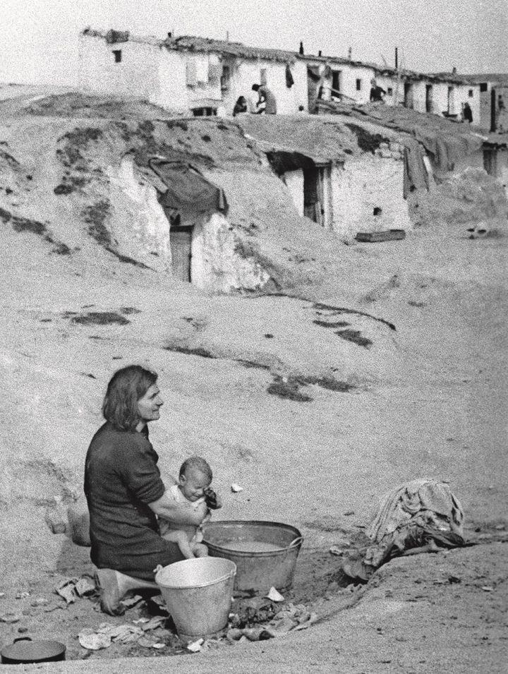 Una mujer baña a su hijo en un balde, en un barrio de chabolas a las afueras de Madrid en abril de 1940. EFE
