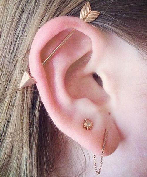 Chica con un piercing en la oreja en forma de flecha