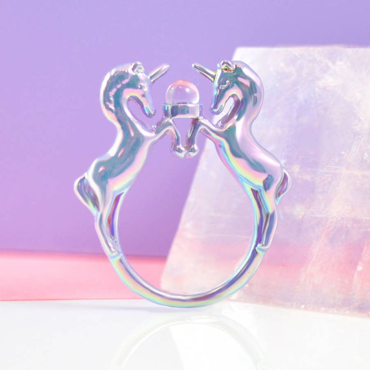 Unicorn ring with lilac iridescent plating by Me & ZenaAlso available gold platedLilac iridescent plated ring by Me & Zena featuring a magical unicorn design, finished with a glass 'crystal ball' stone. Available in S/M & M/L size Me & Zena jewellery is exclusively designed and comes packaged in a Me & Zena branded pillow pack.Lilac plated base metal, glass crystal. Avoid contact with all liquids.S/M: UK size M, US size 6, inner diameter 1.65cm M/L: UK size P, US size 7.5,...