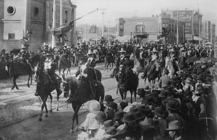 Caballeros and señoras parading on horseback in front of the Plaza Church during La Fiesta de Los Angeles in 1901. Throngs of well-dressed people crowd the sidewalks on both sides of the street. The Grand Marshall of the parade is Francisco Figueroa. The young woman on the horse in black (foreground) is Katie Abbot, daughter of Merced Abbot of Merced Theatre.