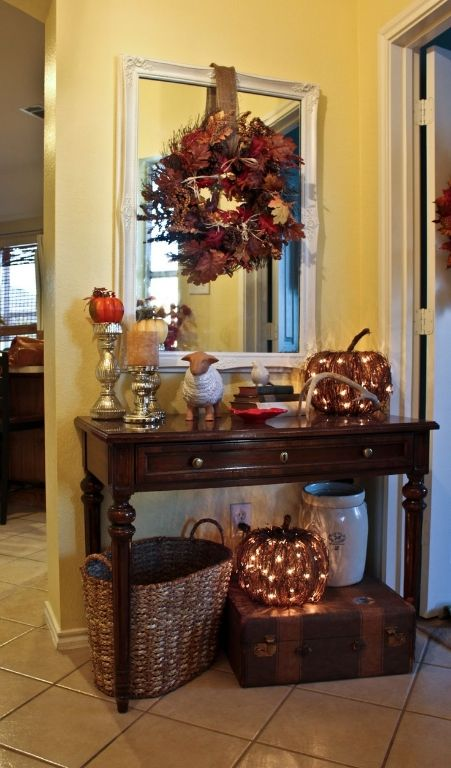 Entry way decorations for fall . I like the idea of lighted pumpkin under the table.