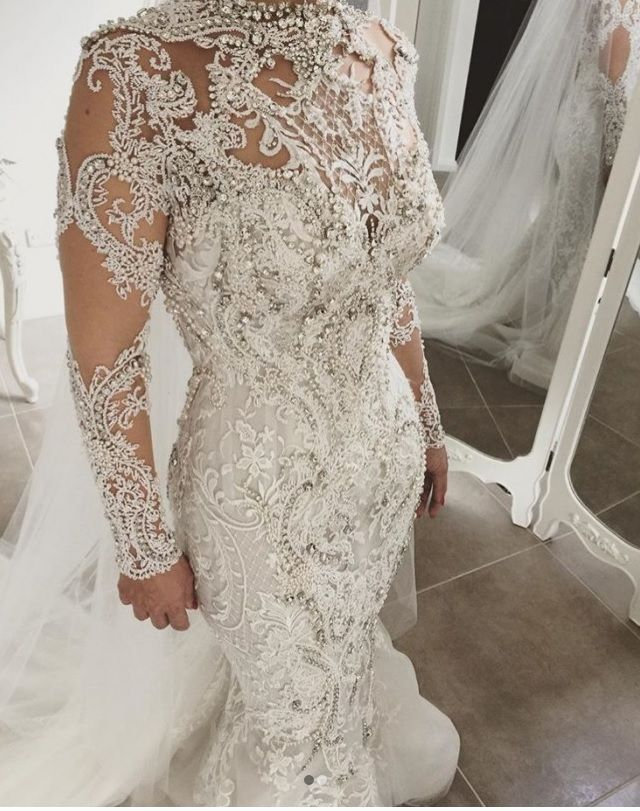 Crystal beaded long sleeve wedding gowns with embroidery can be made in a price range that is affordable.  This elegant sheer sleeve bridal gown is adorned with tons of embroidery and beaded lace.  Custom long sleeve wedding dresses like this can be made to order with any design changes for all sizes.  We also make #replicas of haute couture wedding dresses that will look like the original but cost less.  If your dream dress is pricey email us the images for pricing.
