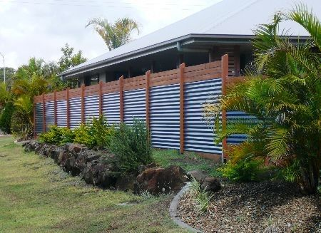 Corrugated metal fence with wood trim, for part of dog kennel