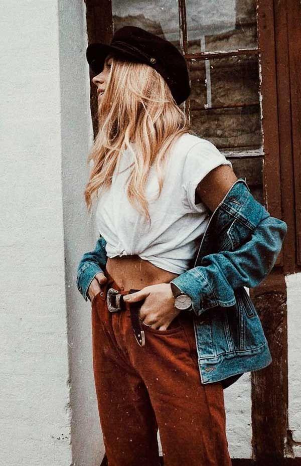 Dar um nozinho na t-shirt deixa o resultado mais fashion e com uma pegada sexy. Aproveite para marcar a cintura com um cinto poderoso. Com calça marrom e jaqueta jeans.