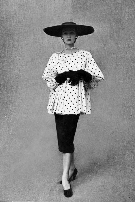 A model wearing a polka dotted smock top over a black skirt by Balenciaga. Photograph by Gordon Parks. Paris, February 1951.