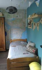 muur beplakt met oude wegenkaarten. staat leuk en stoer op een jongenskamer