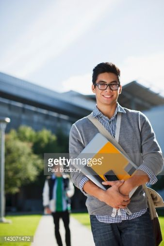 Stock Photo : Student carrying folders outdoors
