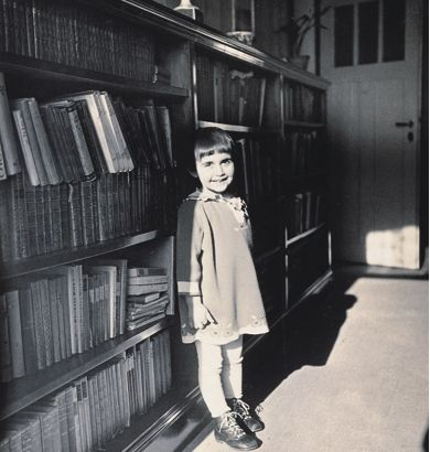Anne Frank as a young child, leaning against bookshelves. I love the light/shadow here... she continues to be a bearer of light.